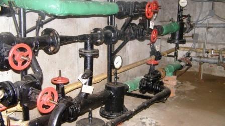 запорная арматура и трубопровод в подвале жилого дома